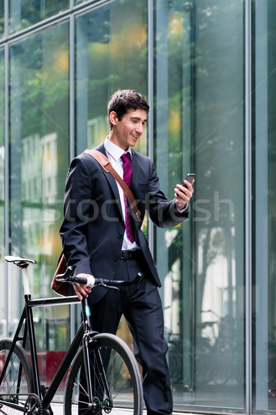 Young confident man  talking on mobile phone after bike commutin Stock photo © Kzenon