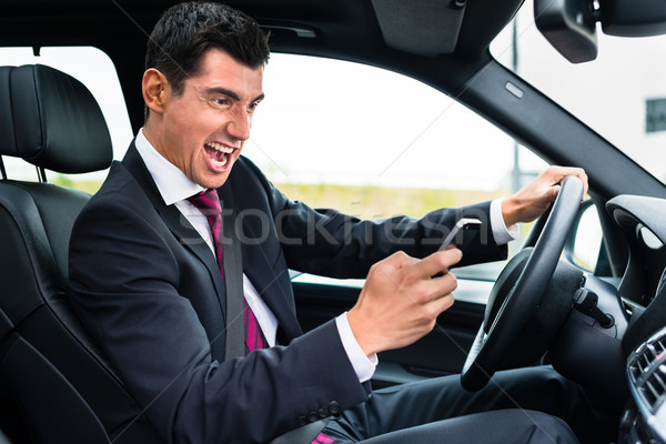 Man texting while driving angrily his car Stock photo © Kzenon