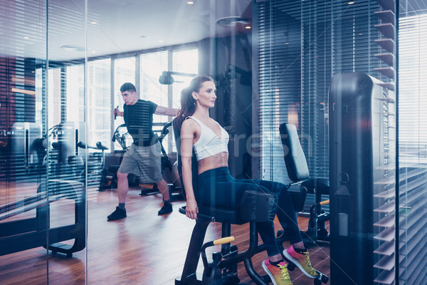 Vrouw fitness gymnasium vergadering machine Stockfoto © Kzenon