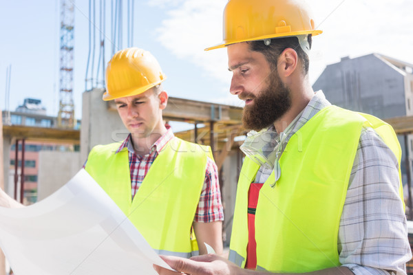 Two young construction workers analyzing together the plan of a  Stock photo © Kzenon