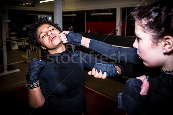 Tough female fighter punching her opponent in the face while pra Stock photo © Kzenon