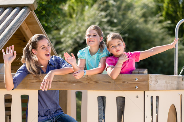 Family with kids playing in tree house on playground Stock photo © Kzenon