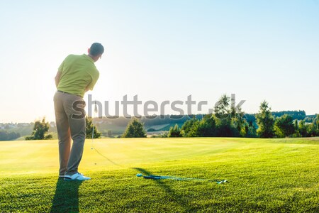 Experienced male golfer hitting the golf ball towards the cup Stock photo © Kzenon