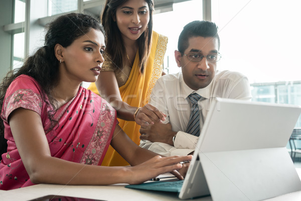 Three Indian employees working together around a laptop  Stock photo © Kzenon