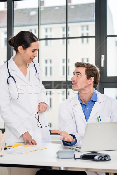 Stock photo: Young female physician asking for advice from her experienced male colleague