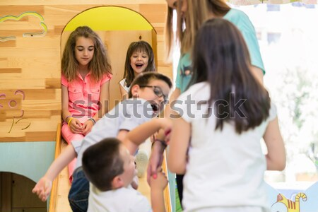 Cute girls smiling during playtime supervised by a young teacher Stock photo © Kzenon
