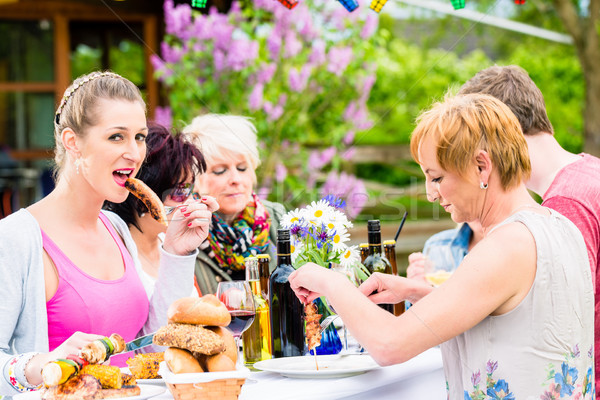 Vrouw eten gegrild worst bbq partij Stockfoto © Kzenon