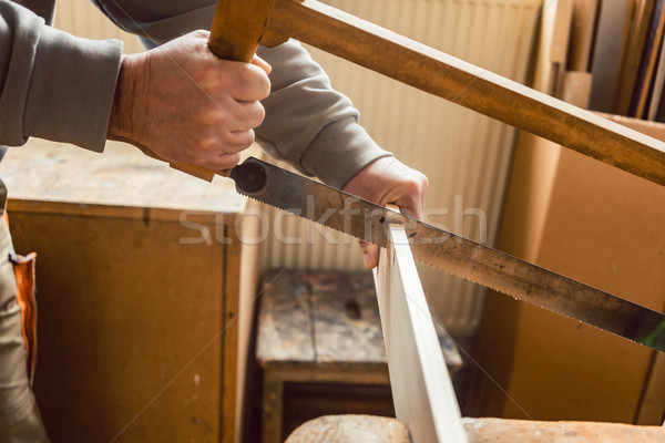 Stock photo: Carpenter working on wood with frame saw