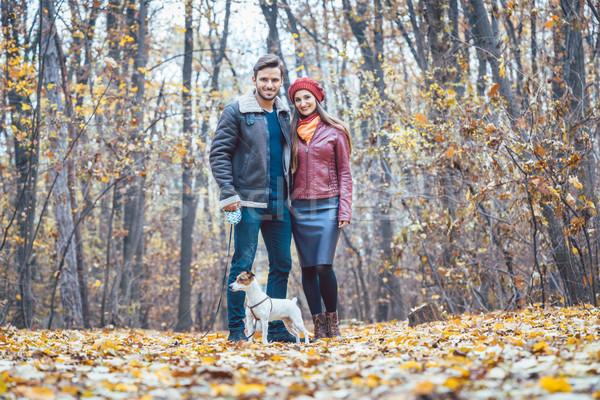 Couple in fall having walk with dog in a park Stock photo © Kzenon