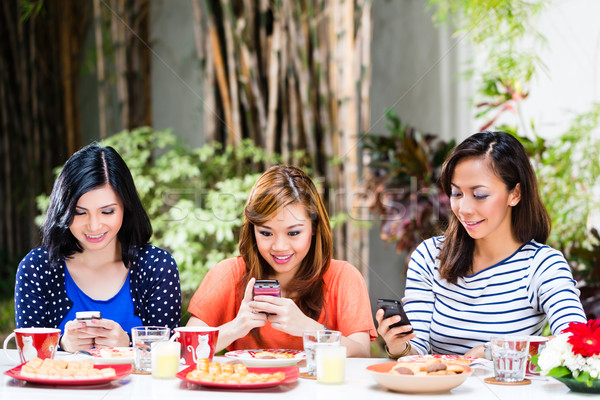 Asian girls using their mobile phones Stock photo © Kzenon
