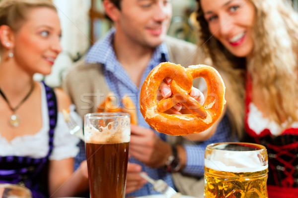 People with beer and pretzel in Bavarian pub Stock photo © Kzenon