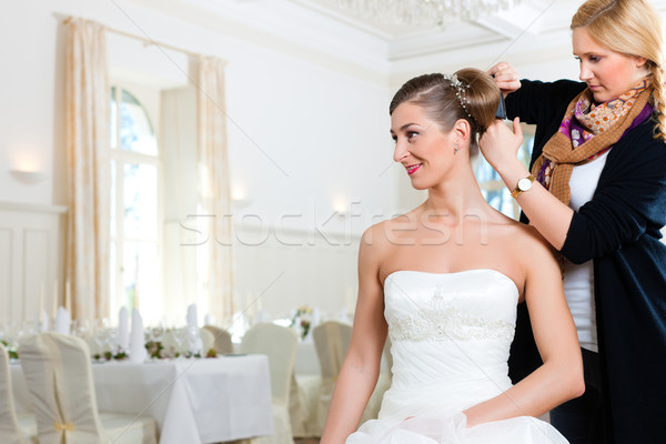 Stylist pinning up a bride's hairstyle Stock photo © Kzenon