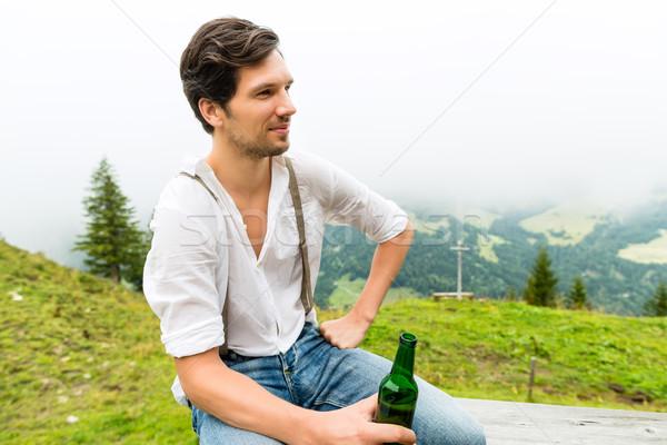 Alps - Man in mountains drinking beer from bottle Stock photo © Kzenon
