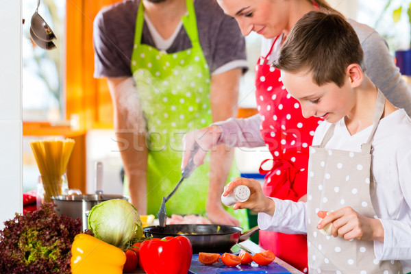 Family cooking healthy food in domestic kitchen  Stock photo © Kzenon