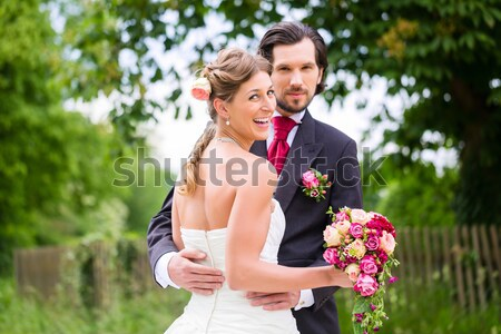 Wedding bride and groom in a meadow, with bridal bouquet Stock photo © Kzenon