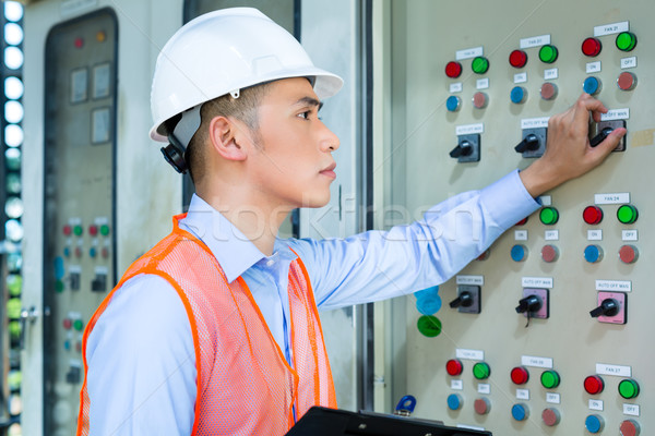 Asian technician at panel on construction site Stock photo © Kzenon