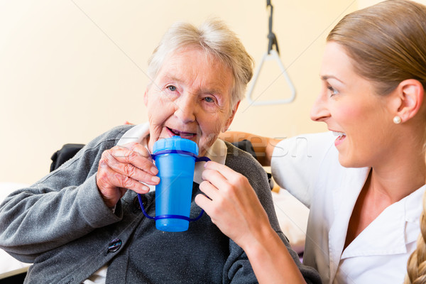 Nurse giving drink to elderly woman in wheelchair Stock photo © Kzenon