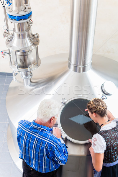 Stock photo: Brewer and couple in beer brewery guided tour