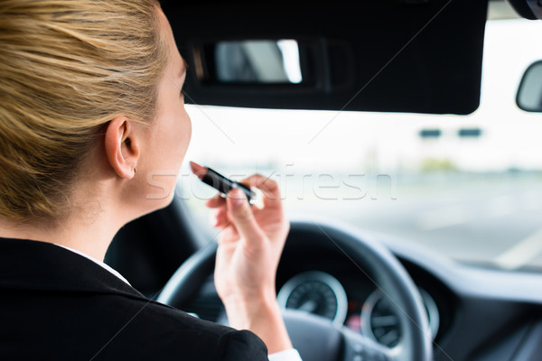 Stock photo: Woman using lipstick while driving her car