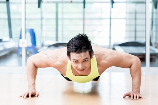 Muscular Asian man doing pushups in gym Stock photo © Kzenon