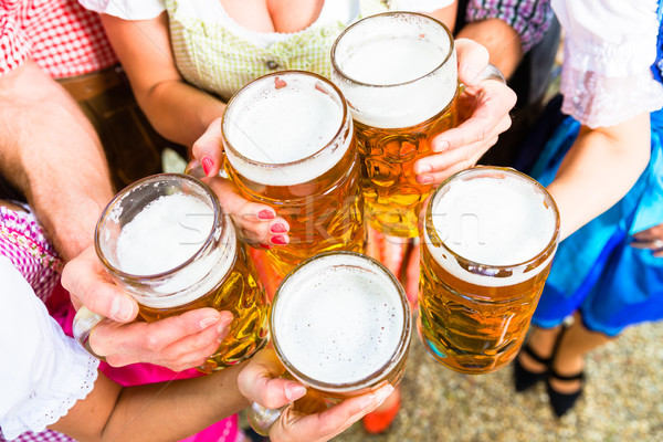 Clinking glasses with beer in Bavarian beer garden Stock photo © Kzenon