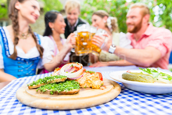 Friends in beer garden with drink and Bavarian appetizers Stock photo © Kzenon
