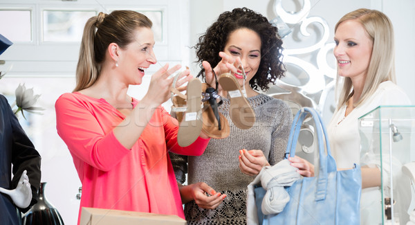 Friends on a shopping trip discussing sandals and buying shoes Stock photo © Kzenon