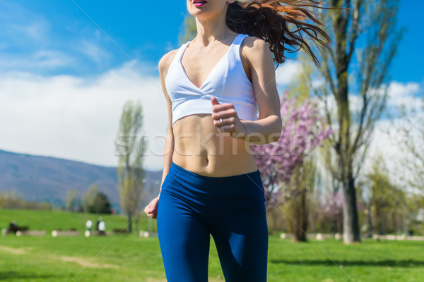 Torso of woman running or jogging on spring day Stock photo © Kzenon