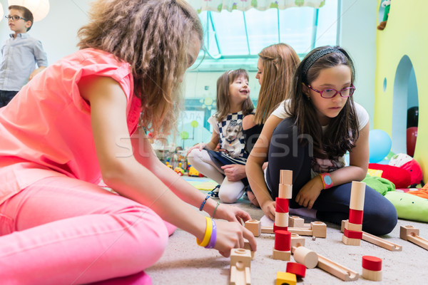 Cute girl building a structure in balance during playtime at the Stock photo © Kzenon