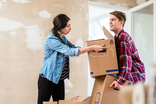 Young woman helping her partner to carry two boxes while moving in Stock photo © Kzenon