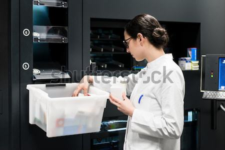 Pharmacist using a computer while managing the drug stock Stock photo © Kzenon