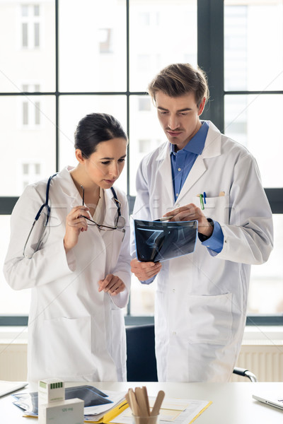Two young dedicated doctors analyzing together the radiograph of a patient Stock photo © Kzenon