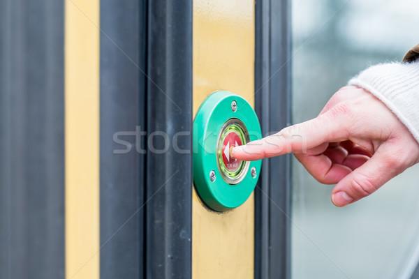 Woman pressing door opener in train Stock photo © Kzenon