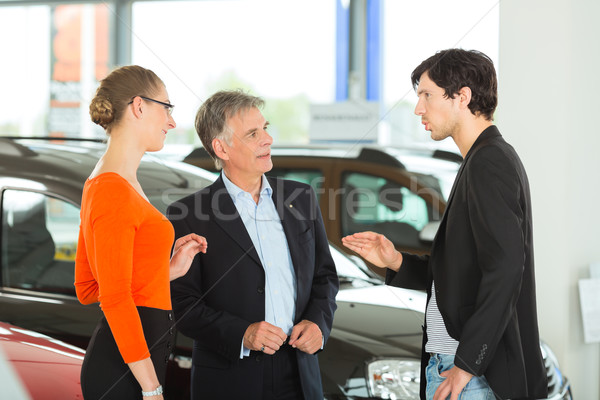 Mature man with young couple and auto in car dealership Stock photo © Kzenon