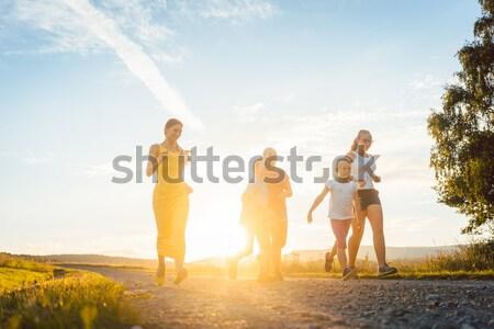 Happy family on meadow at sunset Stock photo © Kzenon