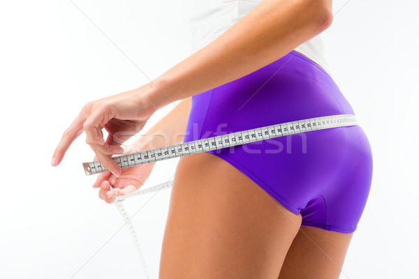 Woman measuring her hip with tape Stock photo © Kzenon