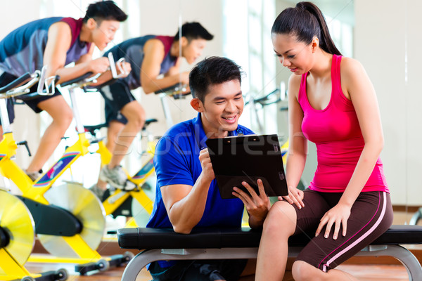 Asian personal trainer with woman in fitness gym Stock photo © Kzenon