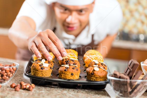 Asian man baking muffins in home kitchen Stock photo © Kzenon