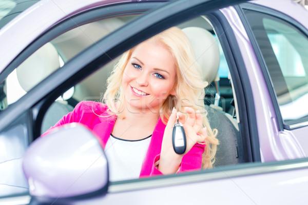 Woman buying new car at dealership showing key Stock photo © Kzenon
