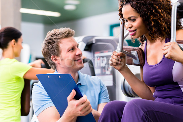 Fitness training in gym - black woman and personal trainer Stock photo © Kzenon