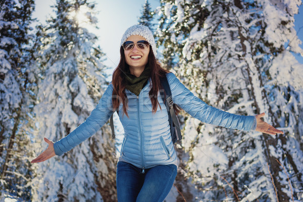 Woman having happy winter walk in snow covered woods Stock photo © Kzenon