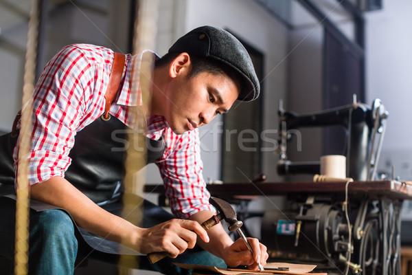 Asian shoe or belt maker in his leather workshop Stock photo © Kzenon
