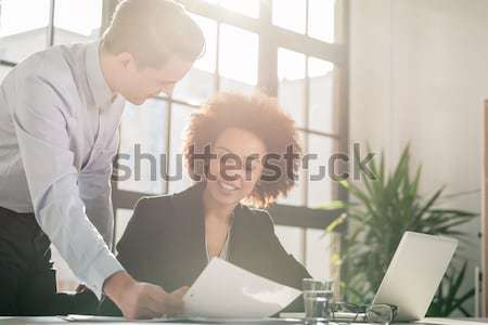 Business man showing to his colleague a document Stock photo © Kzenon