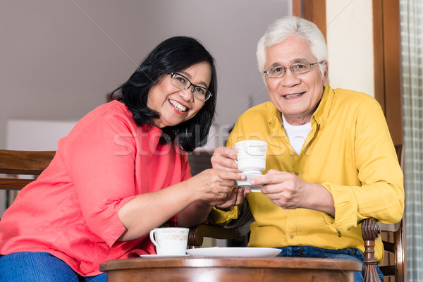 Portrait of serene senior couple enjoying a cup of coffee at hom Stock photo © Kzenon