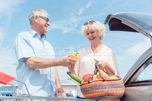 Senior man holding a shopping cart while looking at his wife wit Stock photo © Kzenon