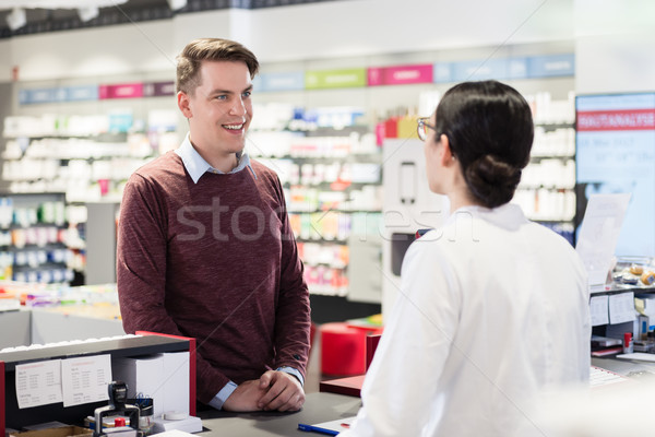 Happy customer listening to the recommendations of a reliable pharmacist Stock photo © Kzenon