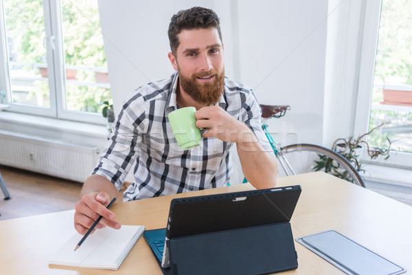 Stock photo: Portrait of a confident self-employed young man sitting at desk