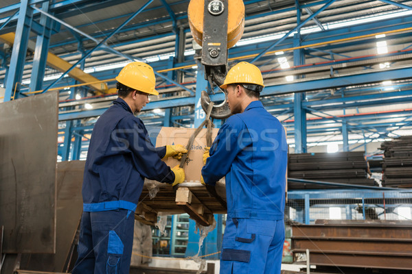 Two workers handling heavy loading lifted by crane Stock photo © Kzenon