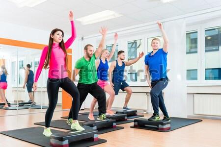 Men and women doing step-aerobics at gym Stock photo © Kzenon