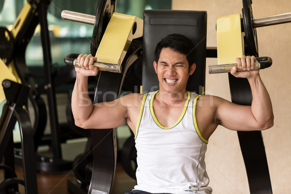 Strong young man exercising for arms muscles at a fitness club Stock photo © Kzenon